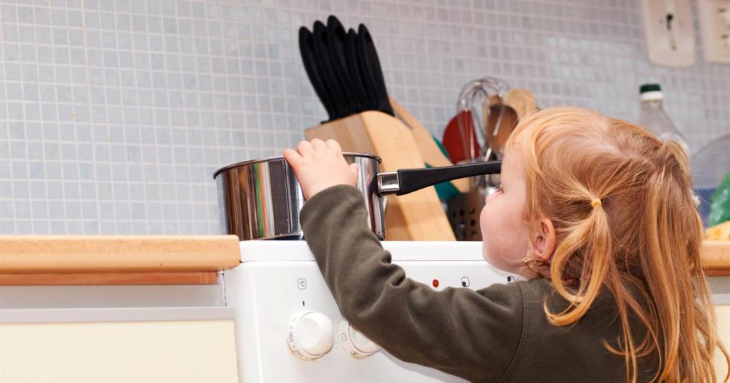 Image of child reaching for pot on stovetop.
